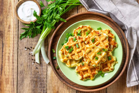 Not sweet waffles with potatoes, peas, bell peppers, cheese are served with sour cream and herbs on a plate on a rustic table. Top view flat lay. Copy space. 免版税图像