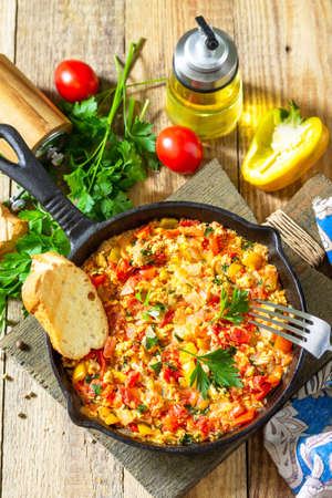 Traditional Turkish dish. Mememen (fried vegetables with scrambled egg) in a cast iron frying pan on a wooden table.
