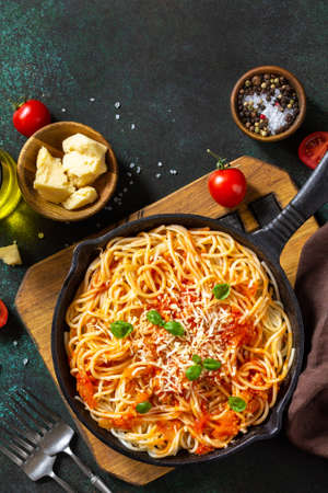 Classic homemade italian spaghetti pasta with tomato sauce, cheese parmesan and basil on dark stone table. Top view, flat lay background. Copy space. 免版税图像