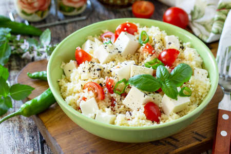 Food dieting concept, tabbouleh salad. Couscous salad with feta cheese, tomatoes, basil and chili on a rustic wooden table.