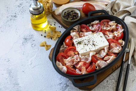 Ingredient for Baked feta pasta, or Tiktok pasta. Oven baked feta pasta made of tomatoes, feta cheese, garlic and herbs. Copy space.
