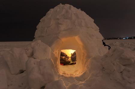 Snow igloo on the frozen sea at night
