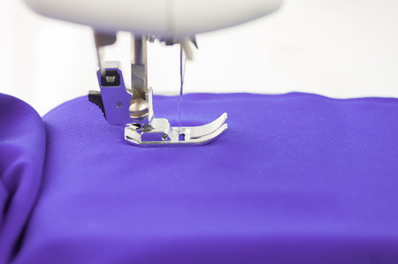 Sewing machine and tissue draped over a white background