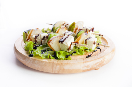 collation: Skewers of cheese, avocado and lettuce on a wooden platter