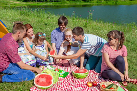 outdoor group portrait of happy family having picnic near the lake and enjoying watermelon photo