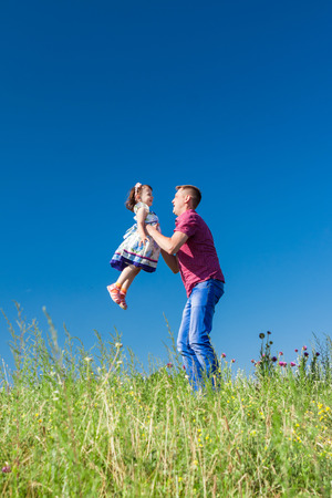 raise your hand: Outdoor portrait of a father who throws daughter in her arms Stock Photo