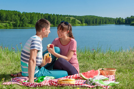 outdoor portrait of happy loving couple having a picnic at the lake photo