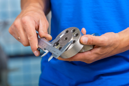 Men's hands with a caliper measuring the size of the details