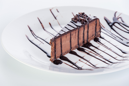 collation: a piece of chocolate cake with topping on a round plate on a white background Stock Photo