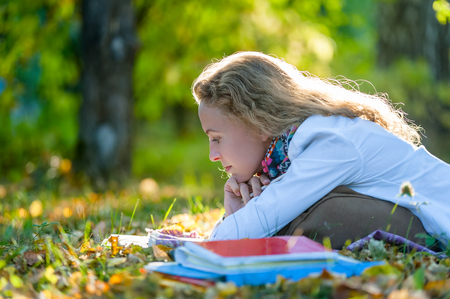 lyrical: Thoughtful student girl is reading in the autumn park