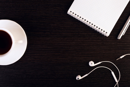 wenge: cup of hot coffee, headphones, notebook, pen on the wooden background. Place for text. Square image.