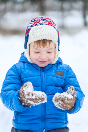 winter park: The little boy looks at the snow-covered mittens in winter park