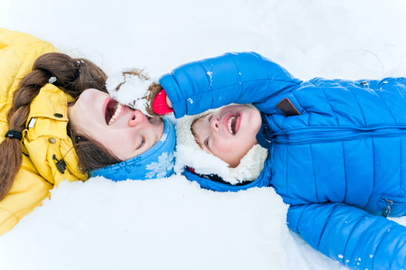 rollick: Happy mother and child lying on the snow in winter park and play Stock Photo