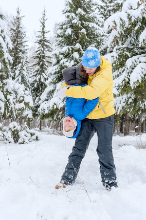 rollick: Outdoor portrait Mom plays with child in winter. She hugging her son