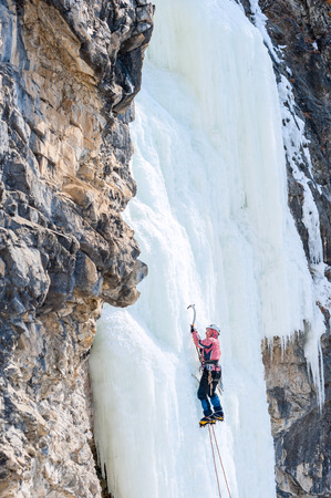 icefall: mountaineer ascends the vertical icefall with ice picks