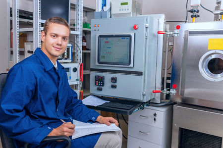manual test equipment: Smiling young male technician records the results of an experiment Stock Photo