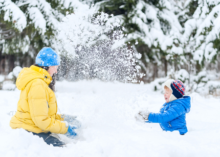 rollick: Outdoor portrait Mother and child playing in the winter park. showered with snow Stock Photo