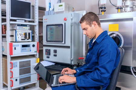 manual test equipment: Young engineer working with a laptop working in a scientific laboratory