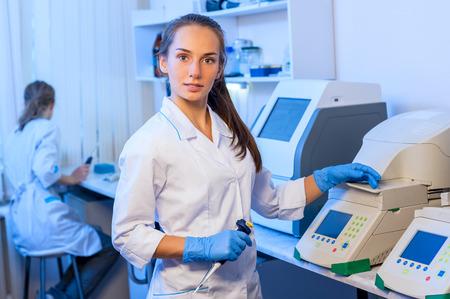 Femme chercheur chimiste dans un laboratoire peignoir blanc travaillant avec des équipements dans le laboratoire moderne