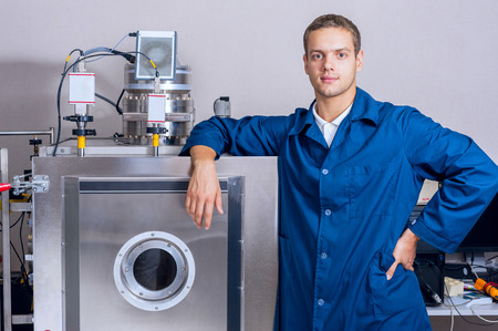 manual test equipment: Young engineer in a scientific laboratory near the vacuum unit