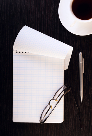 A cup of hot coffee, glasses, notebook, pen on a wooden table. Place for text. Square image.