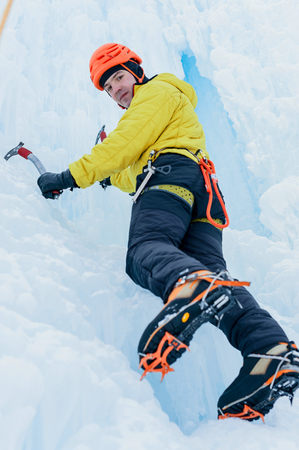 crampon: Athletic alpinist man in orange helmet and ice tools axe climbing a large wall of ice. Outdoor Sports Portrait