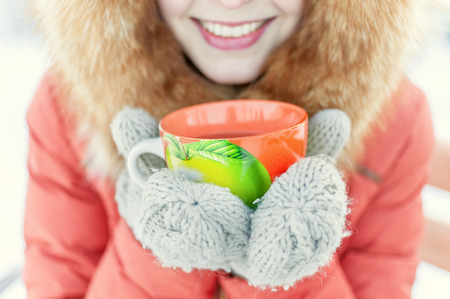 fur hood: Outdoor portrait of a smiling young girl in a fur hood. Drinking tea from an orange mug in the winter park