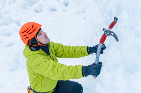 ice axe: Athletic alpinist man in orange helmet and ice tools axe climbing a large wall of ice. Outdoor Sports Portrait