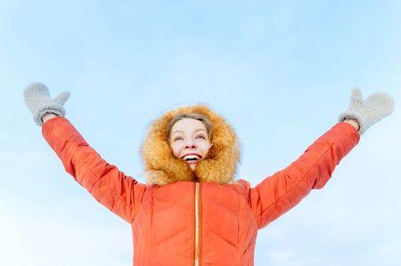 Outdoor-Porträt eines lächelnden Mädchens im Winter Daunenjacke, heben die Hände gegen den blauen Himmel