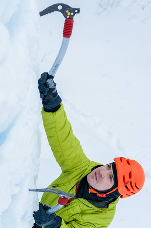 alpinist: Athletic alpinist man in orange helmet and ice tools axe climbing a large wall of ice. Outdoor Sports Portrait