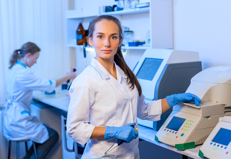 Woman researcher chemist in a white lab bathrobe  working with equipment in the modern laboratory
