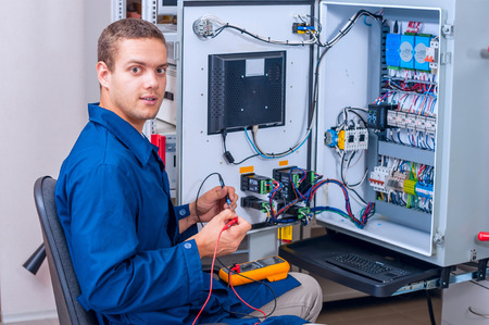 manual test equipment: Engineer working with digital multimeter in the lab