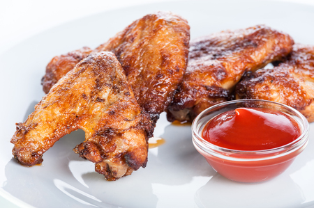 Crispy fried chicken wings with ketchup on a white background