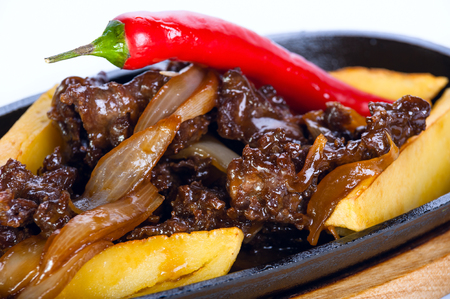 hot frying pan. Roast meat with potatoes and red chili on a white background