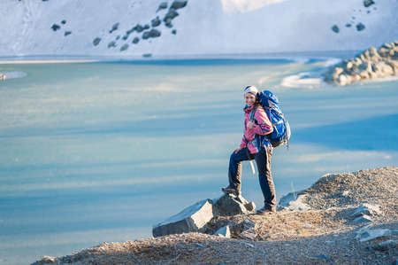 Young girl with backpack standing on the shore of a frozen lake