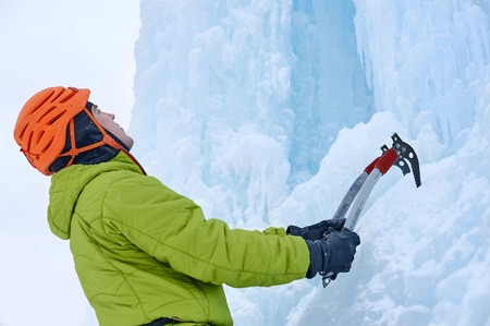 Alpinist man with  ice tools axe in orange helmet climbing a large wall of ice. Outdoor Sports Portrait Stock Photo