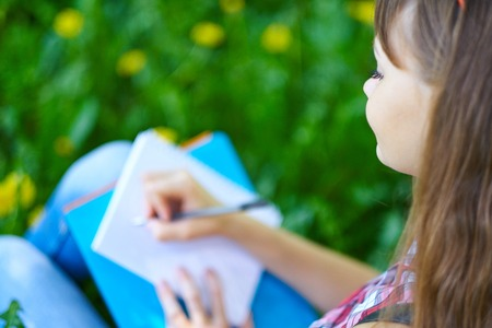 female student writing in notebook in park. Preparation for exams at college or university