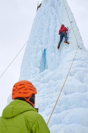 Icebreaker woman with ice tools axe in orange helmet climbing a large wall of ice. Outdoor Sports Portrait