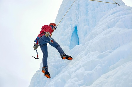 Alpinist woman with  ice tools axe in orange helmet climbing a large wall of ice. Outdoor Sports Portrait Stock Photo