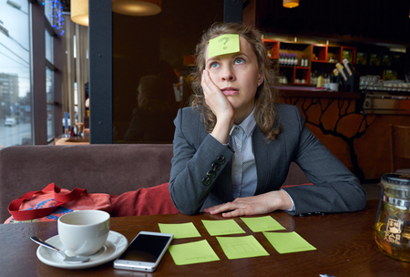 Brainstorm. thinking tired woman with question mark. Sticker on forehead. Concept portrait search for an answer to a question Imagens