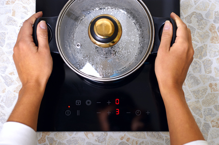 Women hand put pan in modern kitchen with induction stove Imagens