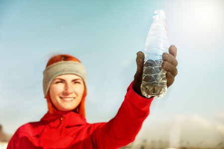 Young woman with bottle of water after jogging in winter park Stock Photo
