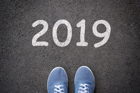 Dlue jeans casual shoes standing on the asphalt concrete road and white sign to new year 2019 Stock Photo