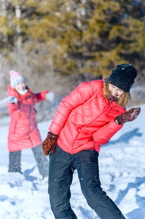 Outdoor portrait of two young girls in bright jackets, playing snowballs in a winter park. having fun throwing snow