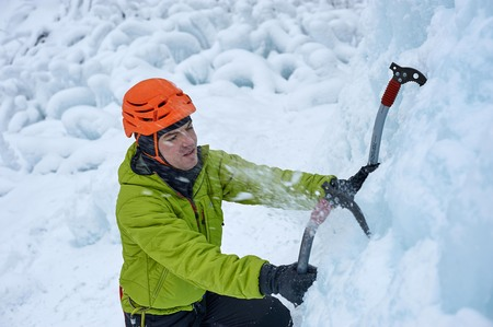 Alpinist man with  ice tools axe in orange helmet climbing a large wall of ice. Outdoor Sports Portrait Reklamní fotografie