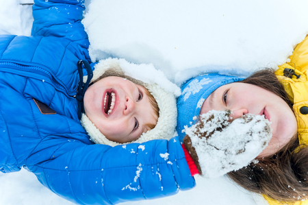 Outdoor portrait Happy mother and child lying on the snow in winter park and play Stock Photo