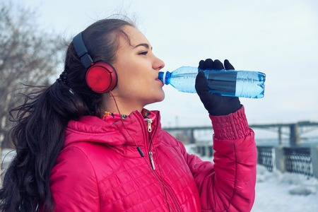 Drinking during sport. Young woman drinking water after run