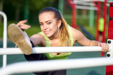 Portrait of fit and sporty young woman doing stretching in workout sports ground. Stockfoto - 122913690
