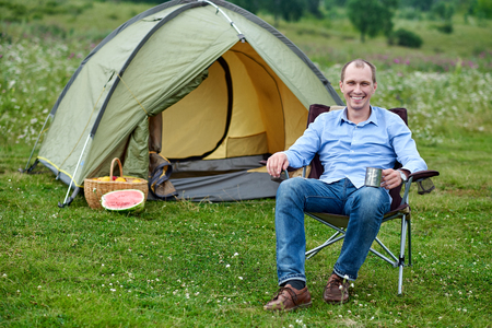 young man freelancer sitting on chair and relaxing in front of tent at camping site in forest or meadow. Outdoor activity in summer. Adventure traveling in national park. leisure, vacation, relaxation