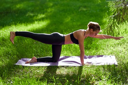 Yoga. Young woman practicing yoga meditation in nature at the park. Health lifestyle concept. 写真素材